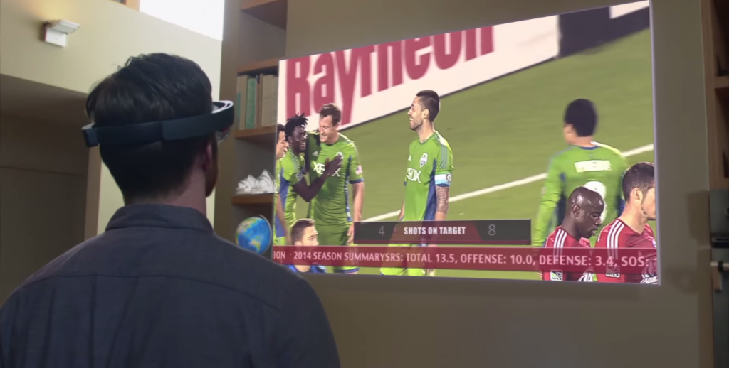 Screenshot of Microsoft's HoloLens promo video shows a man watching a soccer game on a virtual TV.